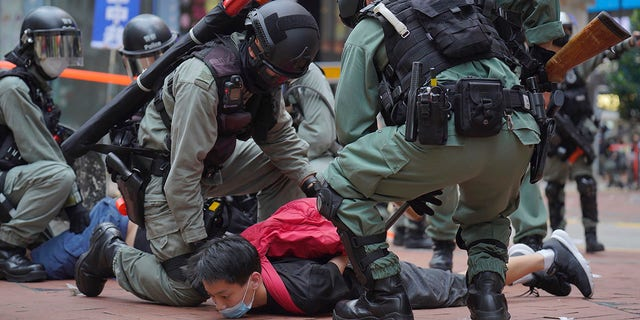 Riot police detain a protester during a demonstration against Beijing's national security legislation in Causeway Bay in Hong Kong, Sunday, May 24, 2020. (AP Photo/Vincent Yu)