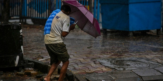 A man struggles to hold his umbrella and walk against high wind in Kolkata, India, May 20, 2020.