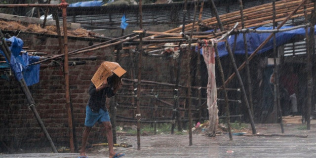 A man covers him head with a box and walks in the rain ahead of Cyclone Amphan landfall, at Bhadrak district, in the eastern Indian state of Orissa, May 20, 2020.
