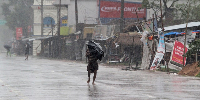 People walk with umbrellas in the rain ahead of Cyclone Amphan landfall, at Bhadrak district, in the eastern Indian state of Orissa, May 20, 2020.