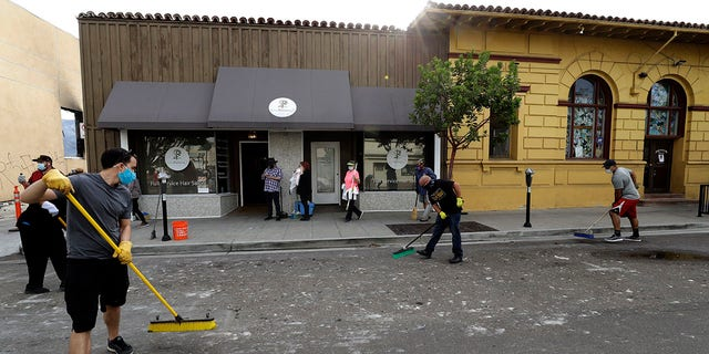 People helping clean up broken glass and debris after the riots over the death of George Floyd, Sunday in La Mesa, Calif. (AP Photo/Gregory Bull)