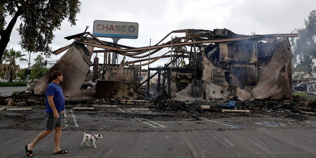 A man passing the Chase bank burned in the riots. (AP Photo/Gregory Bull)