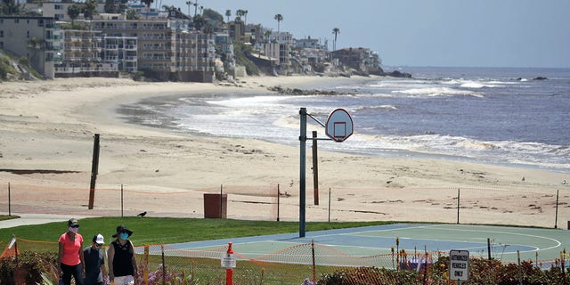 Residents walk past a closed off beach, in Laguna Beach, Calif., on Sunday. The cities of Laguna Beach and San Clemente reopened their beaches this week after they submitted plans to avoid overcrowding and allow for physical distancing in an effort to prevent the spread of the coronavirus. (AP Photo/Marcio Jose Sanchez,File)