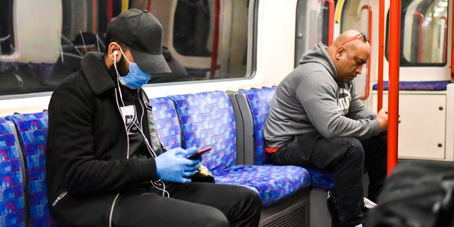 A man sits on a London underground train wearing a protective mask, in London, Tuesday, May 12, 2020. Britain's Prime Minister Boris Johnson announced Sunday limited changes to the national lockdown to limit the spread of the COVID-19 coronavirus.