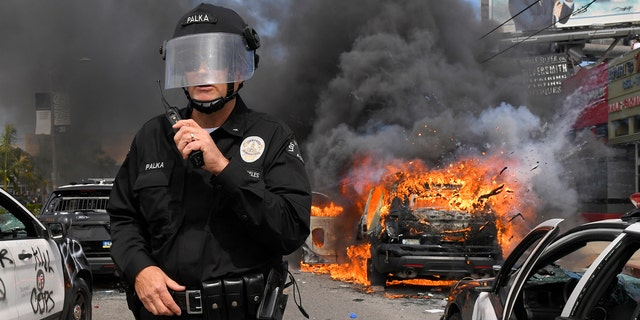 Los Angeles Police Department commander Cory Palka stands among several destroyed police cars as one explodes while on fire during a protest over the death of George Floyd, Saturday, May 30, 2020, in Los Angeles.