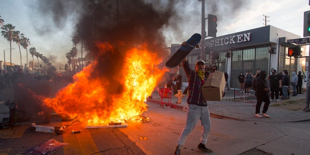 A protester shouts in front of a fire during a protest over the death of George Floyd, a handcuffed black man in police custody in Minneapolis, in Los Angeles, Saturday, May 30, 2020.