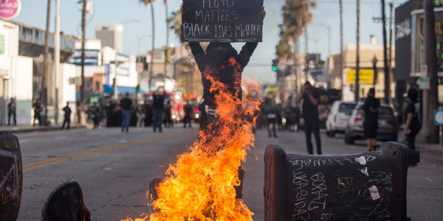A protester holding a sign stands behind the burning trash cans during a protest over the death of George Floyd, a handcuffed black man in police custody in Minneapolis, in Los Angeles, Saturday, May 30, 2020.