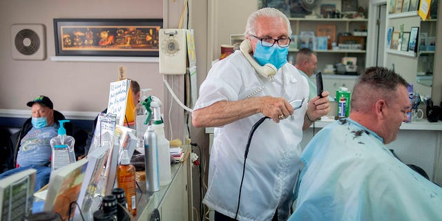 Manke has given over 100 haircuts, and fields more calls than that daily, all while continuing to cut hair. He has followed sanitary measures while working, including wearing a mask and sanitizing his tools with ultraviolet light.(Jake May/The Flint Journal via AP)