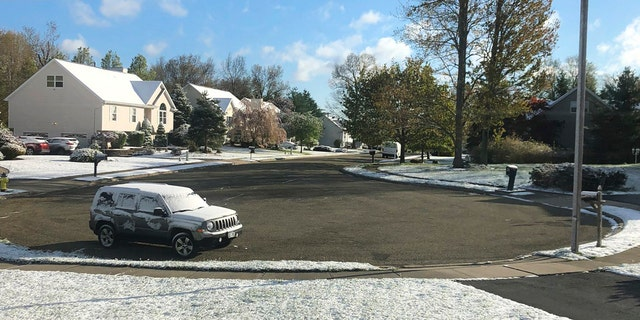 In this photo provided by Robert Beretta, snow accumulates on the grass and vehicles in Monroe, N.Y., Saturday, May 9, 2020.
