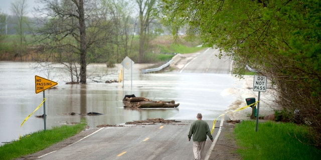Freeland resident Cyndi Ballien walks up to get a closer look as heavy rain floods North Gleaner Road near its intersection with Tittabawassee Road on Tuesday, May 19, 2020, in Saginaw County, Mich.
