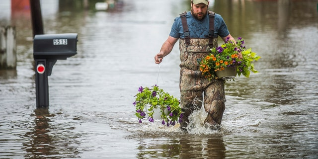 Tyler Marciniak, of Grand Rapids, carries hanging plants through floodwaters as he helps his father, Tom Marciniak, assess the damage to his home on Red Oak Drive on Wixom Lake, Tuesday, May 19, 2020, in Beaverton, Mich.