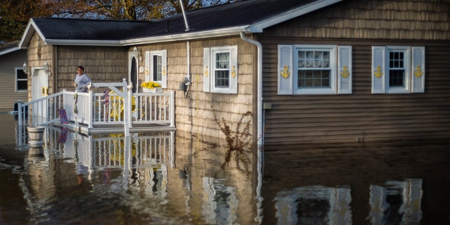 Carol Ouellette stands on her front porch, surrounded by floodwater, Tuesday, May 19, 2020 in Beaverton, Mich.