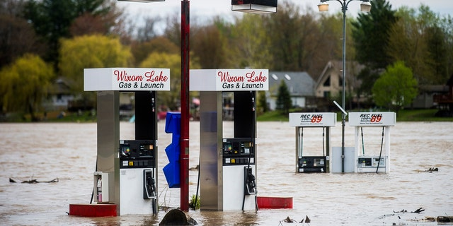 Floodwater surrounds gas pumps at Wixom Lake Gas & Launch May 19, along the Tittabawassee River in Beaverton, Mich.