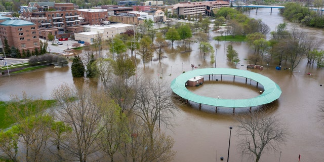 Water floods the Midland Area Farmers Market and the bridge along the Tittabawassee River in Midland, Mich., on May 19.