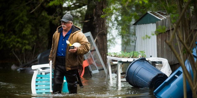 Mark Musselman brings a chair to the front of his house from the back yard, wading through floodwater, May 19, in Edenville, Michigan.