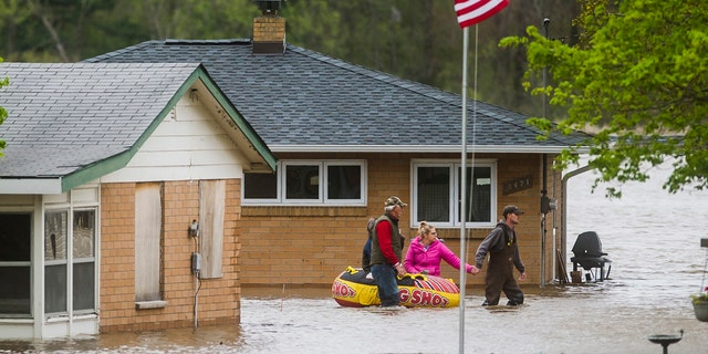 People help each other travel from one home to another using an inflatable raft on Oakridge Road on Wixom Lake, May 19, in Beaverton, Michigan.