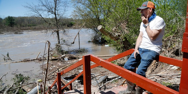 Dan Dionne looks over his former deck outside his home, May 20, in Edenville, Mich.