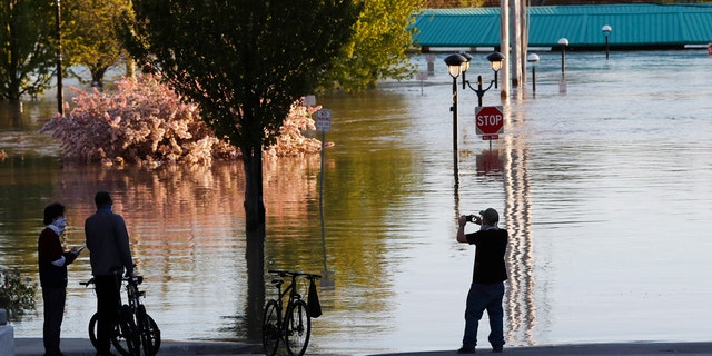 People photograph the floodwaters of the Tittabawassee River that encroached on downtown Midland, Mich., May 20.