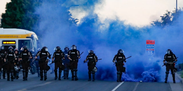 Police in riot gear prepares to advance on protesters, Saturday, May 30, 2020, in Minneapolis.