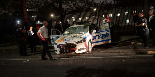 Policemen surround a NYPD vehicle after it was vandalized by protestors over the death of George Floyd, a black man who was in police custody in Minneapolis, on Saturday, May 30, 2020, in the Brooklyn borough of New York. Floyd died after being restrained by Minneapolis police officers on Memorial Day.