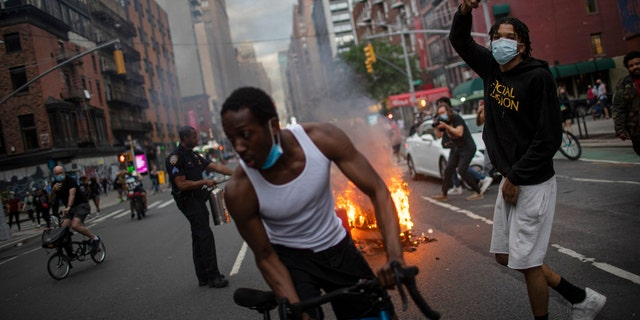 Protesters march down the street as trash burns in the background during a solidarity rally for George Floyd, Saturday, May 30, 2020, in New York.
