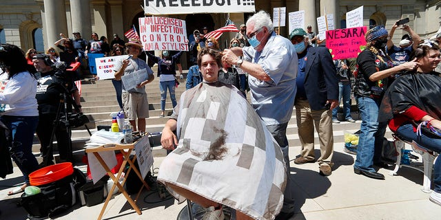 Barber Karl Manke, of Owosso, gives a free haircut to Parker Shonts on the steps of the State Capitol during a rally in Lansing, Mich., on Wednesday. (AP Photo/Paul Sancya)