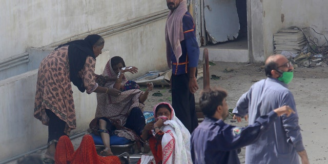Residents of an area hit by a plane crash wait for medical help in Karachi, Pakistan, Friday, May 22, 2020.
