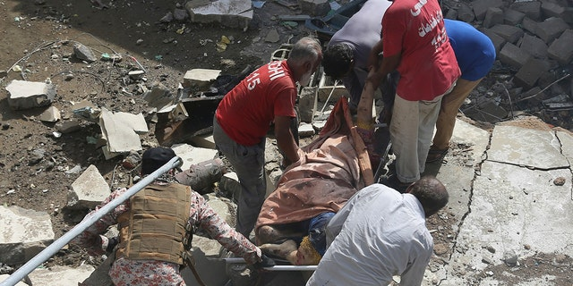 Volunteers carry the dead body of a plane crash victim at the site of a crash in Karachi, Pakistan, Friday, May 22, 2020.