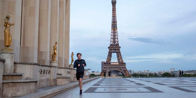 A man runs past some statues wearing face masks along the Trocadero square close to the Eiffel Tower during the coronavirus pandemic on Saturday. (AP Photo/Rafael Yahgobzadeh)