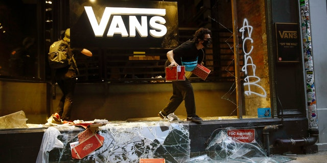 A person jumps from a storefront that had its window broken during the Justice for George Floyd Philadelphia Protest on Saturday, May 30, 2020.
