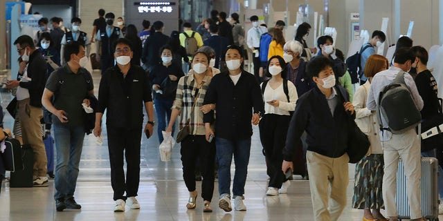 People wearing face masks arrive at the domestic flight terminal of Gimpo airport in Seoul, South Korea, on Wednesday. The quarantine authorities on Wednesday began to require all airplane passengers to wear masks amid the coronavirus pandemic. (AP Photo/Ahn Young-joon)