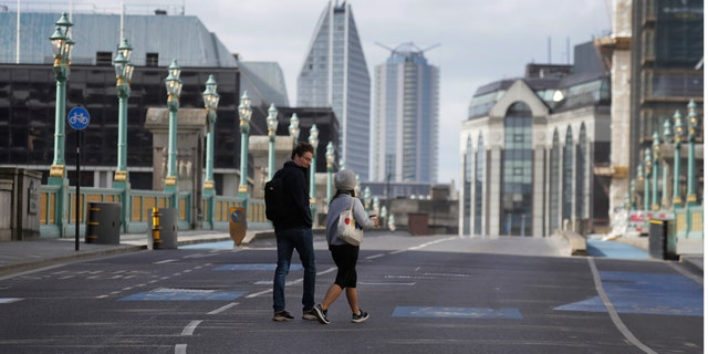 Pedestrians cross the road on Southwark Bridge during the morning rush hour in London as the country continues in lockdown to help stop the spread of coronavirus, Monday, May 11, 2020. Britain's Prime Minister Boris Johnson announced Sunday that people could return to work if they could not work from home. (AP Photo/Kirsty Wigglesworth)