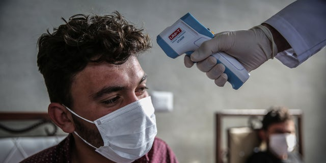A medic checks the temperature of a man inside a health isolation centre which has been established on the Syrian-Turkish borders in order to place people coming from Turkey to Idlib as a preventive measure against the spread of the coronavirus disease (COVID-19).