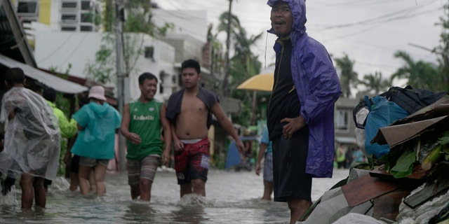 Residents wade along a flooded village caused by typhoon Vongfong as it passed by Sorsogon province, eastern Philippines on Friday May 15, 2020.