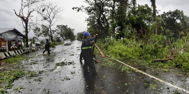 Workers clear a road of trees and branches toppled by strong winds from typhoon Vongfong as it passes by Sorsogon province, eastern Philippines on Friday May 15, 2020.
