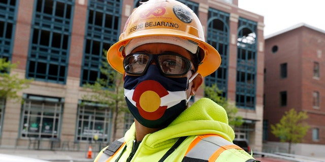 Construction worker Jesus Bejarano wears a face mask bearing the design of the flag of Colorado, as workers report to their jobs for the first time in nearly two months with the expiration of the city's stay-at-home order to check the spread of the new coronavirus May 9, in Denver. (AP Photo/David Zalubowski)