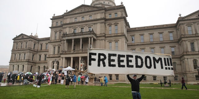 A protester carries a sign during a rally against MichiganÕs coronavirus stay-at-home order at the State Capitol in Lansing, Mich., Thursday, May 14, 2020. (AP Photo/Paul Sancya)