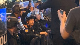 Phoenix police kneel with peaceful protesters chanting 'take a knee' as crowd disbands for curfew