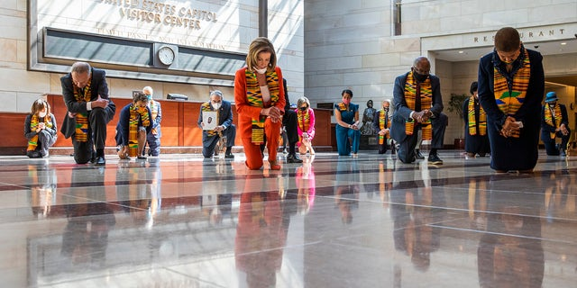 House Speaker Nancy Pelosi of Calif., center, and other members of Congress, kneel and observe a moment of silence at the Capitol's Emancipation Hall, Monday, June 8, 2020, on Capitol Hill in Washington, reading the names of George Floyd and others killed during police interactions.