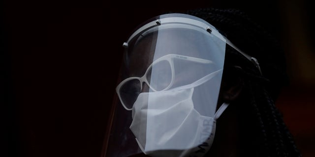 A woman wearing a face mask and shield to protect from the spread of the new coronavirus in Duque de Caxias, Brazil, Wednesday, June 10, 2020. (AP Photo/Silvia Izquierdo)