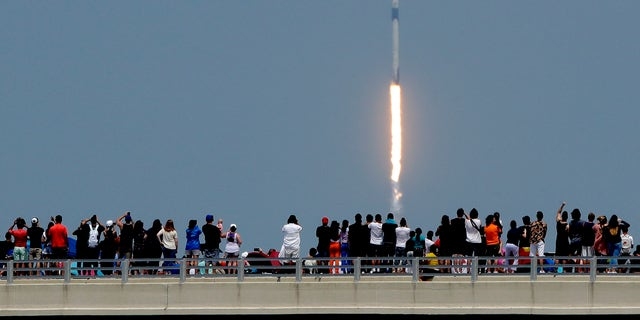 Spectators watch from a bridge in Titusville, Fla., as SpaceX Falcon 9 lifts off with NASA astronauts Doug Hurley and Bob Behnken in the Dragon crew capsule, Saturday, May 30, 2020, from the Kennedy Space Center at Cape Canaveral, Fla.  (AP Photo/Charlie Riedel)