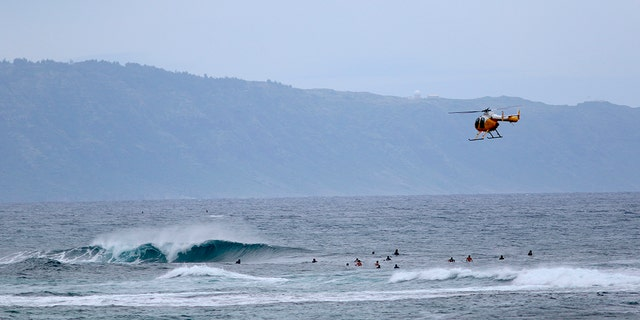 A fire and rescue helicopter flies over a group of surfers on Oahu's North Shore near Haleiwa, Hawaii on March 31, 2020. (AP Photo/Caleb Jones,File)