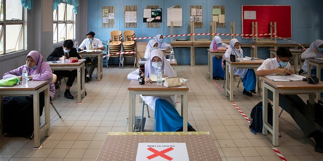 Students wearing face masks and maintaining social distancing at a classroom during the first day of school reopening at a high school in Putrajaya, Malaysia, Wednesday, June 24, 2020. Malaysia began reopening schools Wednesday while entering the Recovery Movement Control Order (RMCO) after three months of coronavirus restrictions. (AP Photo/Vincent Thian)