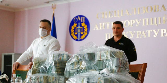Ukraine's Anti-Corruption Prosecutor Nazar Kholodnytsky, left, and National Anti-Corruption Bureau chief Artem Sytnik displaying the massive piles of cash at an anti-corruption prosecutor's office in Kiev on Saturday.