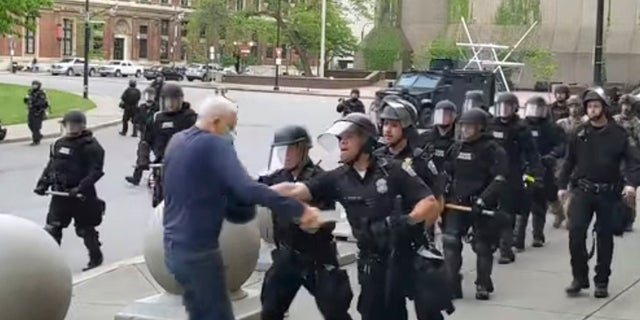 """A Buffalo police officer appears to shove Martin Gugino, who walked up to police during a June 4 demonstration. Video from WBFO shows Gugino appearing to hit his head on the pavement, with blood leaking out as officers walk past to clear Niagara Square. Buffalo police initially said in a statement that a person """"was injured when he tripped & fell,"""" WIVB-TV reported. (Mike Desmond/WBFO via AP)"""