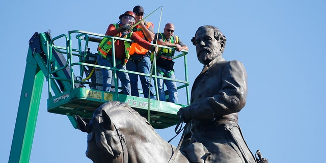 An inspection crew from the Virginia Department of General Services takes measurements as they inspect the statue of Confederate Gen. Robert E. Lee on Monument Avenue Monday June 8, 2020, in Richmond, Va. (AP Photo/Steve Helber)