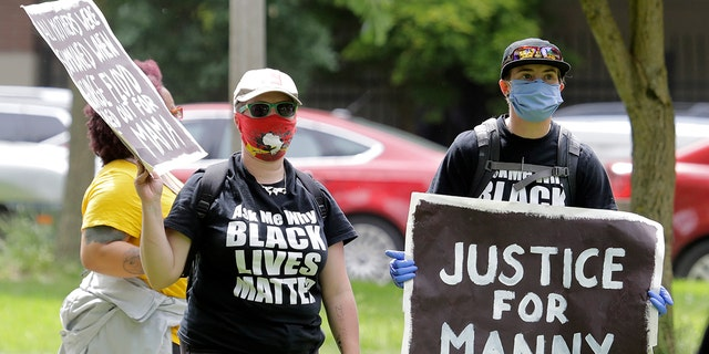 """A protester holds a sign that reads """"Justice for Manny"""" on June 5, in Tacoma, Wash., during a protest against police brutality and the death of George Floyd, a black man who died after being restrained by Minneapolis police officers on May 25. Ellis died March 3 while being held down by Tacoma police. (AP Photo/Ted S. Warren)"""