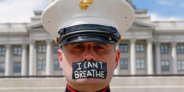 "Retired Marine Todd Winn, wearing a mask that reads ""I Can't Breathe,"" participates in a protest in front of the Utah State Capitol in Salt Lake City on Friday, June 5, 2020, amid protests around the world in the wake of the death of George Floyd. (AP Photo/Rick Bowmer)"