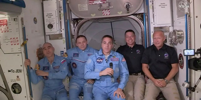 This photo provided by NASA shows Bob Behnken and Doug Hurley, far right, joining the crew at the International Space Station, after the SpaceX Dragon capsule pulled up to the station and docked Sunday, May 31, 2020. The Dragon capsule arrived Sunday morning, hours after a historic liftoff from Florida. It's the first time that a privately built and owned spacecraft has delivered a crew to the orbiting lab. (NASA via AP)