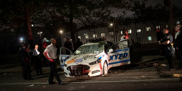 Policemen surround an NYPD vehicle after it was vandalized by protestors over the death of George Floyd, a black man who was in police custody in Minneapolis, on Saturday in the Brooklyn borough of New York. Floyd died after being restrained by Minneapolis police officers on Memorial Day. (AP Photo/Wong Maye-E)